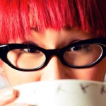 woman with red hair and black pair of glasses, drinking a cup of coffee, symbolizing the importance of showing up