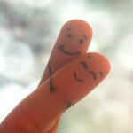 two fingers, painted with faces, symbolizing the important of relationship advice books