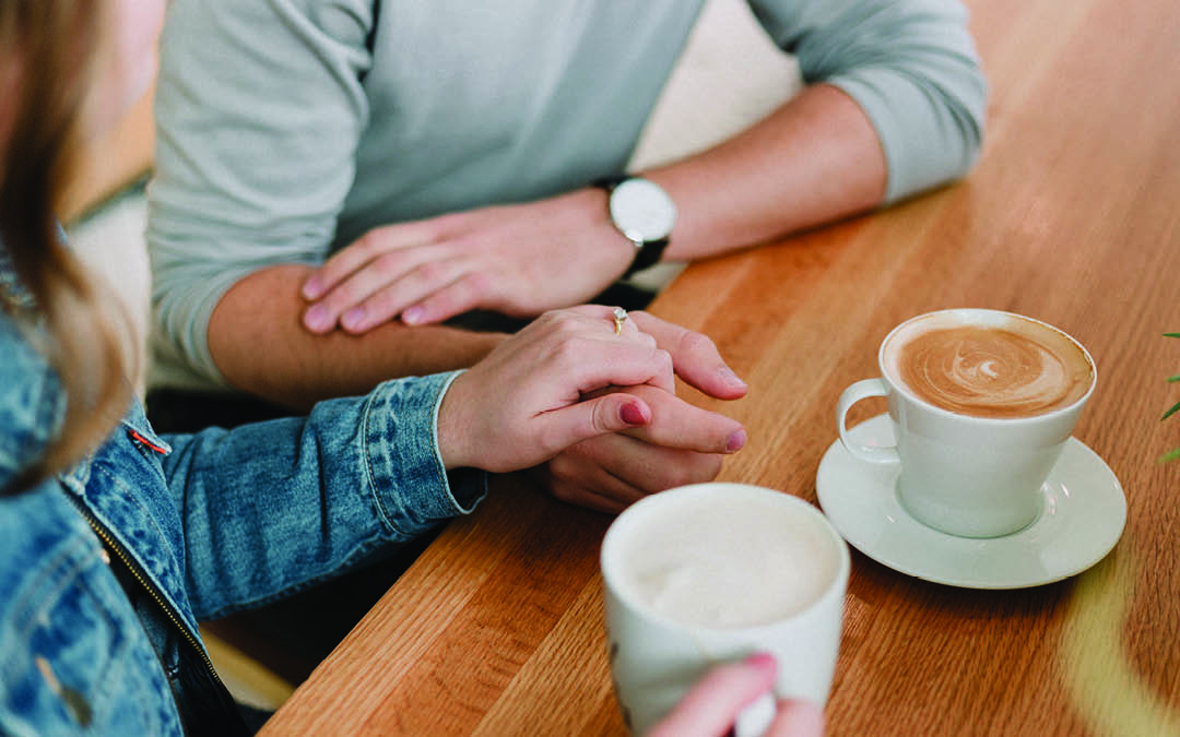 couple sitting on a wooden table, holding hands and drinking coffee, how to communicate better with your partner
