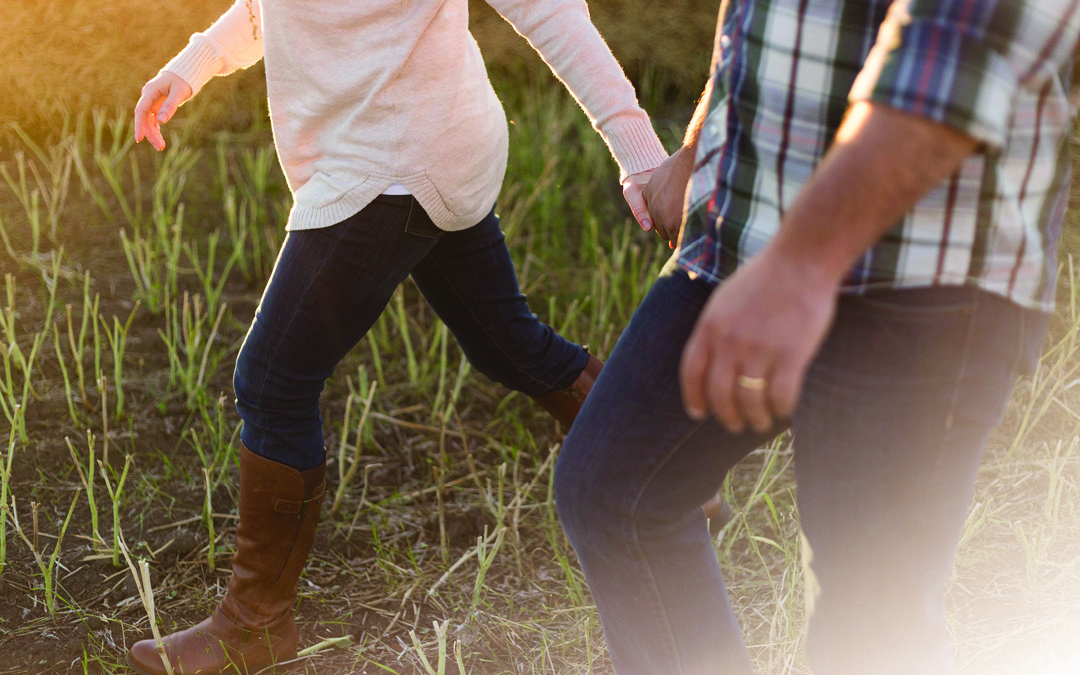 a couple walking through a field and holding hands, how to reconnect to your partner
