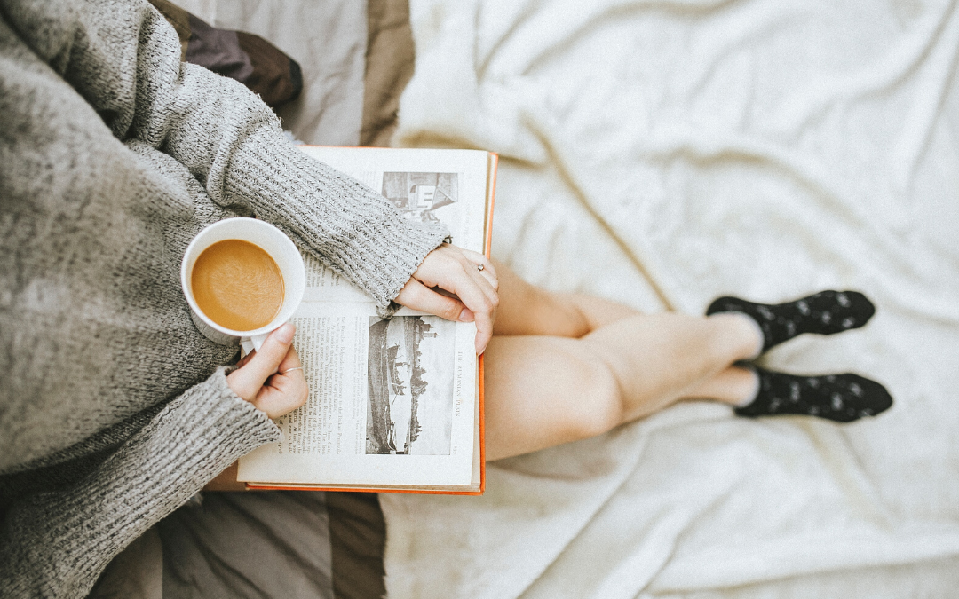 woman sitting on her bed, wearing a long pullover and socks, holding her coffee and a book in her hands, are you an emotional caretaker